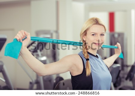 Happy Fit Woman with Blond Hair Stretching Towel Behind her Head at the Fitness Gym. - stock photo