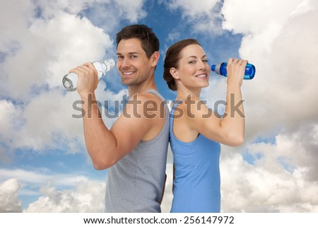 Happy fit young couple with water bottles against blue sky with white clouds - stock photo