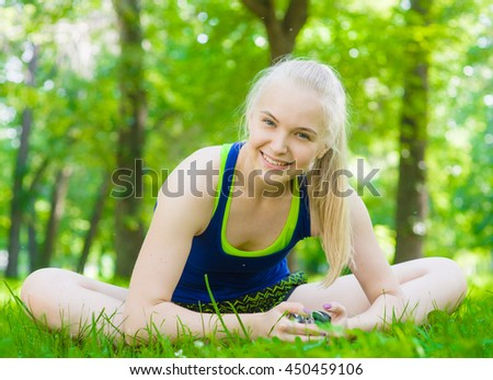 Happy fitness woman butterfly stretching legs in outdoor summer park - stock photo