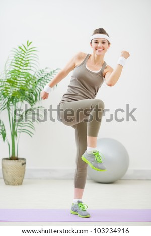 Happy fitness woman making gymnastics - stock photo