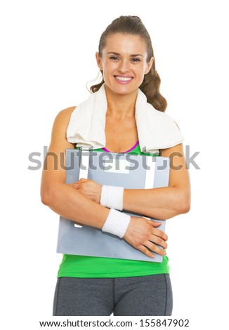 Happy fitness young woman hugging scales - stock photo