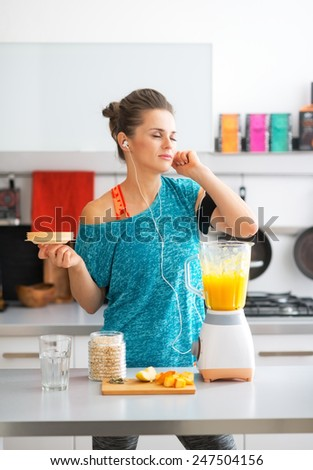 Happy fitness young woman making pumpkin smoothie in kitchen and listening music
