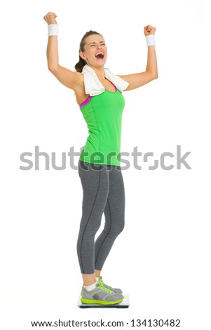 Happy fitness young woman standing on scales and rejoicing success - stock photo