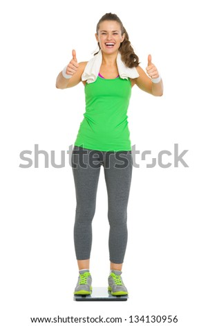 Happy fitness young woman standing on scales and showing thumbs up - stock photo