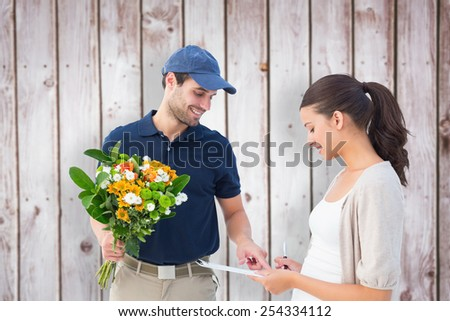 Happy flower delivery man with customer against wooden planks - stock photo