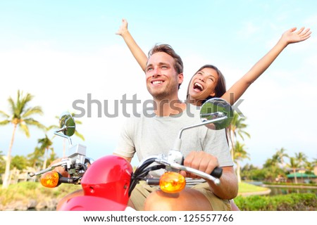 Happy free freedom couple driving scooter excited on summer holidays vacation. Young multiethnic couple, Asian woman, Caucasian man - stock photo