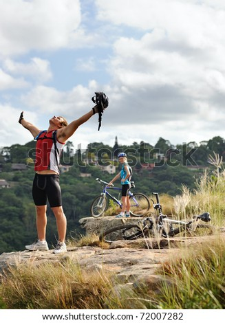 happy free fun man stands victorious on a mountain with arms outstretched and helmet in hand - stock photo