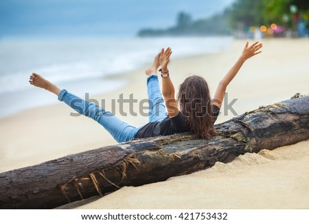 happy freedom woman with hands up and legs up cheering on the tropical beach - stock photo