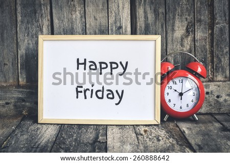 Happy Friday message on white board and red retro clock  by wooden background. - stock photo