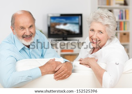 Happy friendly elderly couple relaxing in their living room in front of the television turning to smile at the camera over the back of the sofa - stock photo