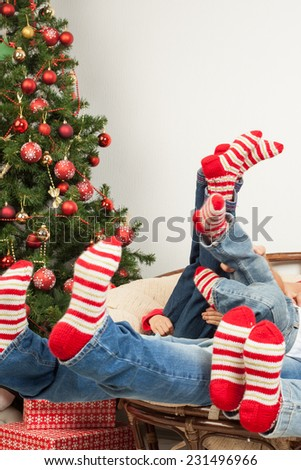 Happy friendly family in knit socks having fun at Christmastime - stock photo