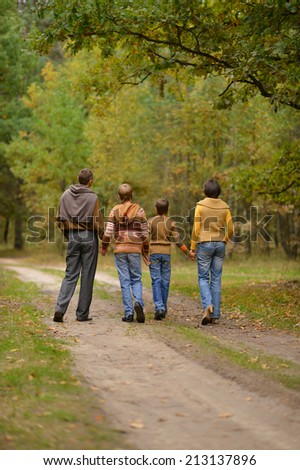 Happy friendly family walking in autumn forest