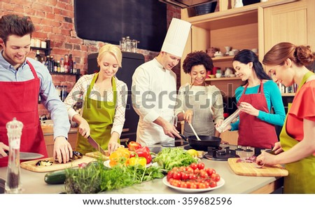 happy friends and chef cook cooking in kitchen - stock photo