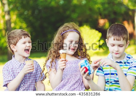 Happy friends. Children enjoy eating ice cream in summer park. - stock photo