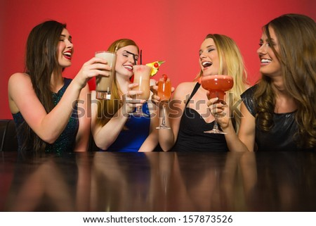 Happy friends clinking glasses and chatting in a nightclub