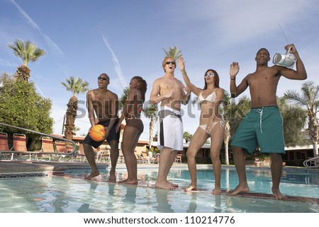 Happy friends dancing at the pool - stock photo