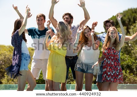 Happy friends dancing near the swimming pool on a sunny day - stock photo