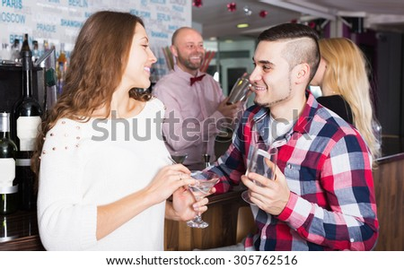 Happy friends drinking and chatting with positive adult barman at bar counter - stock photo