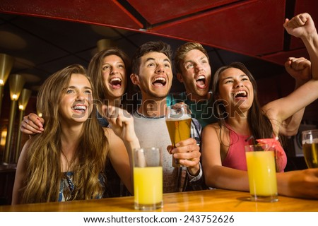 Happy friends drinking beer and cheering together in a bar - stock photo