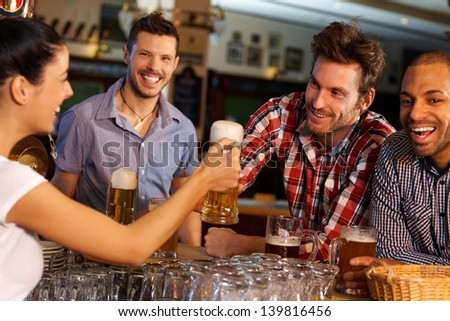 Happy friends drinking beer at counter in pub, chatting with female bartender, smiling. - stock photo