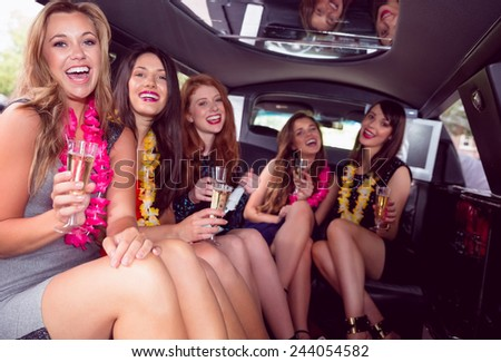Happy friends drinking champagne in limousine on a night out - stock photo
