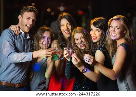 Happy friends drinking shots smiling at camera at the nightclub - stock photo