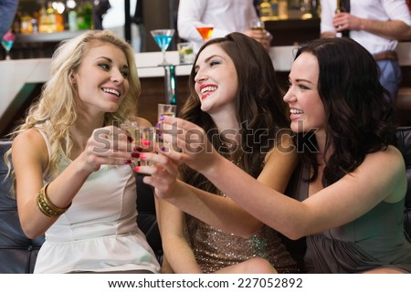 Happy friends drinking shots together at the bar