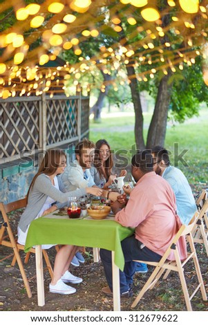 Happy friends eating Thanksgiving dinner outdoors - stock photo