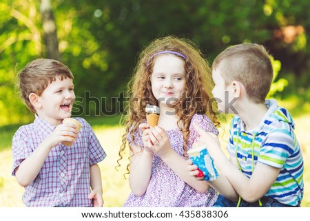 Happy friends  enjoy eating ice cream in summer park. - stock photo
