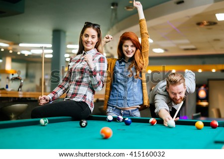 Happy friends enjoying playing pool together - stock photo