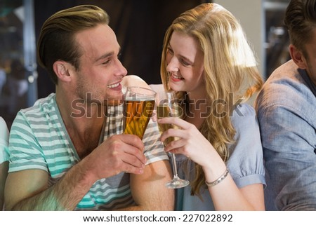Happy friends having a drink together at the bar - stock photo