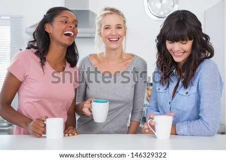 Happy friends having coffee together at home in kitchen - stock photo