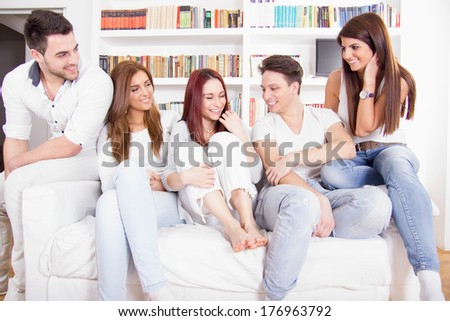 happy friends having conversation on sofa at home with library and books behind - stock photo