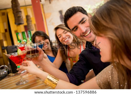 Happy friends having drinks at the bar and toasting - stock photo