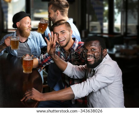 Happy friends having fun and drinking beer in pub - stock photo