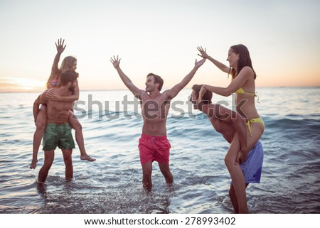 Happy friends having fun in the water at the beach - stock photo