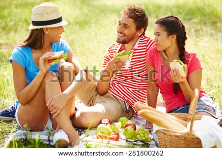 Happy friends having picnic in natural environment - stock photo