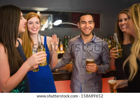 Happy friends holding beers and chatting in the nightclub - stock photo