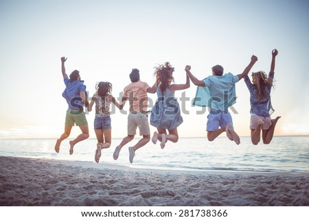 Happy friends holding hands and jumping at the beach - stock photo
