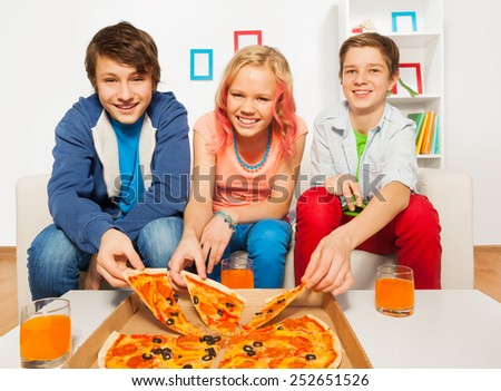 Happy friends holding tasty pizza pieces at home - stock photo