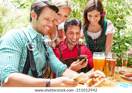 Happy friends in beer garden looking together at smartphones - stock photo
