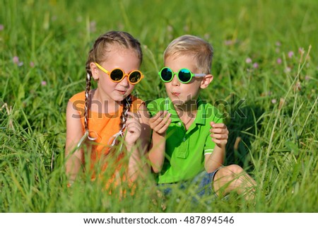 Happy friends in sun glasses having fun in grass outdoors. happy childhood, friendship