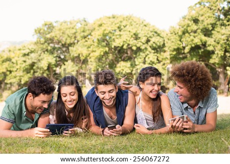 Happy friends in the park using their phones on a sunny day - stock photo