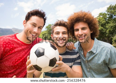 Happy friends in the park with football on a sunny day - stock photo