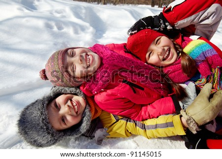 Happy friends in winterwear looking at camera while lying in snow - stock photo