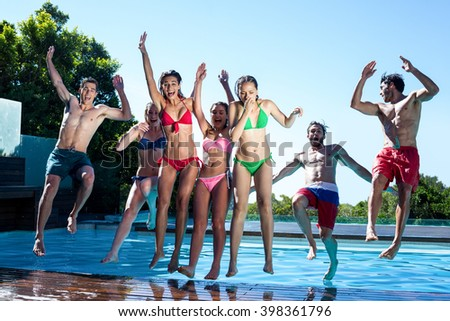 Happy friends jumping in swimming pool on a sunny day - stock photo