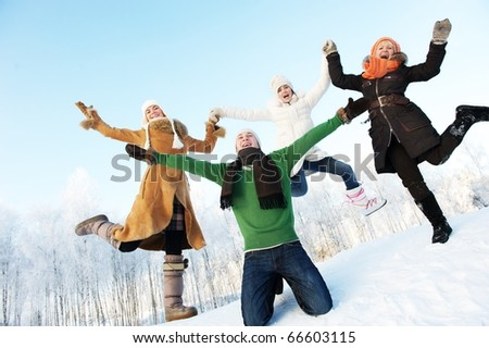 Happy friends jumping in the snow - stock photo