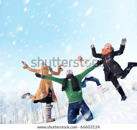 Happy friends jumping in the snow