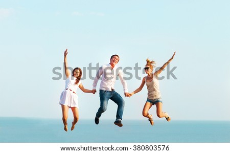 Happy friends jumping on the beach. Summer time