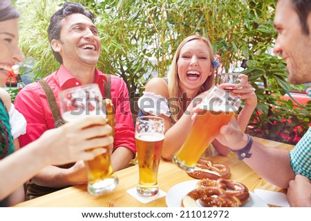 Happy friends laughing in beer garden in summer in Bavaria - stock photo